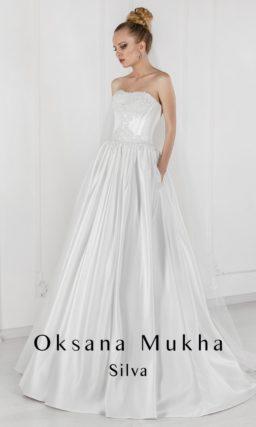Атласное свадебное платье с юбкой А-силуэта, дополненной скрытыми карманами.