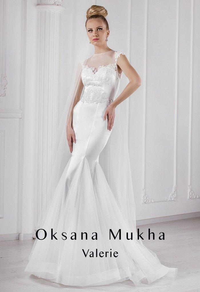 Закрытое свадебное платье «рыбка» из атласной ткани с пышной полупрозрачной отделкой.