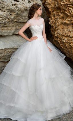 Закрытое свадебное платье с пышной юбкой, покрытой оборками.