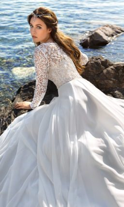 Свадебное платье силуэта «принцесса» с глубоким вырезом и длинными рукавами.