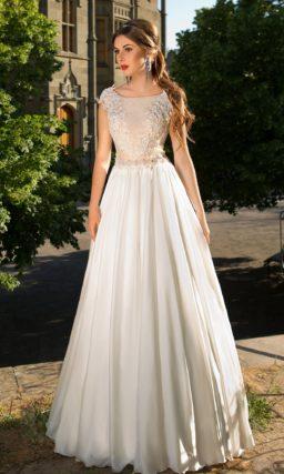 Свадебное платье с юбкой А-силуэта и облегающим закрытым верхом, декорированным аппликациями.