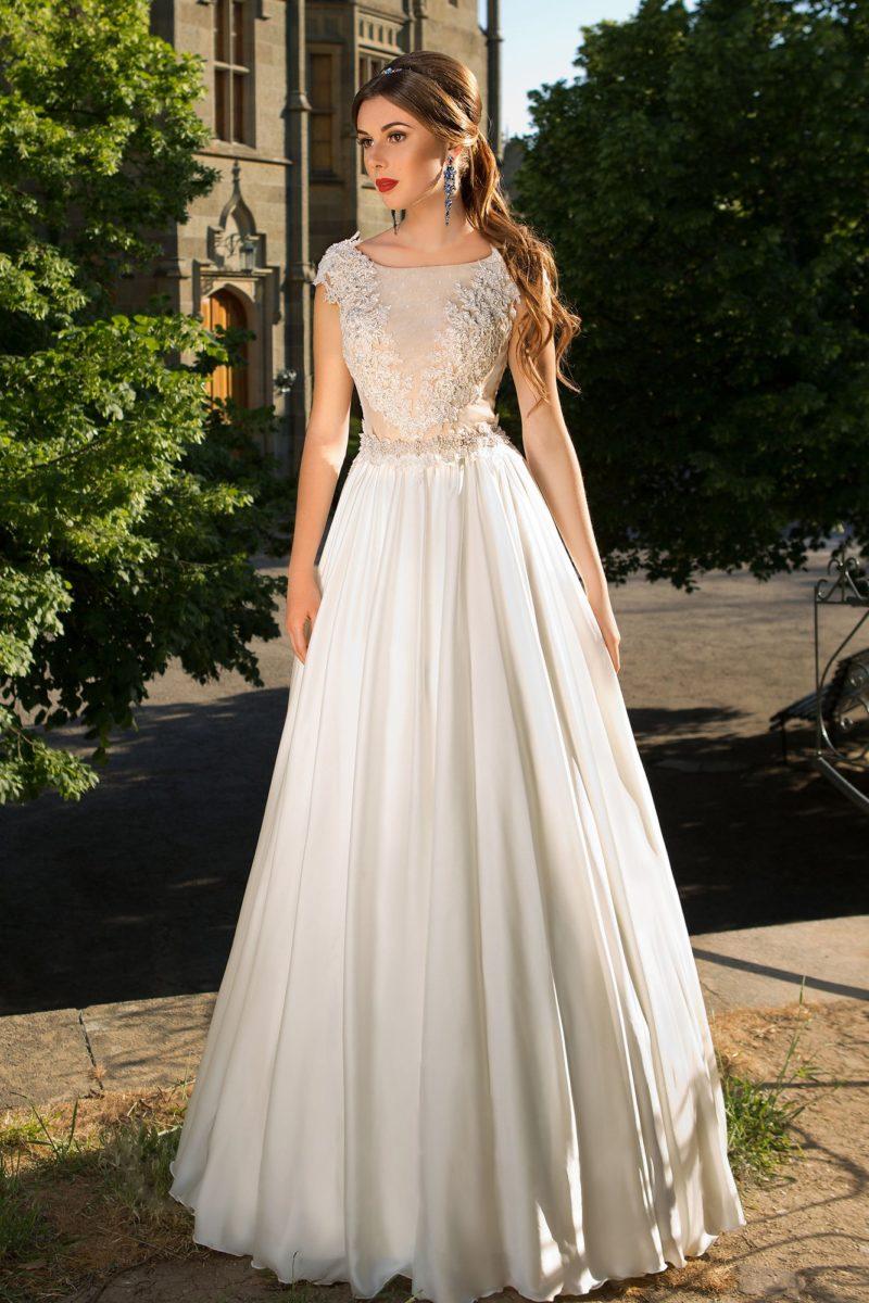 Свадебное платье с облегающим закрытым верхом, декорированным аппликациями.