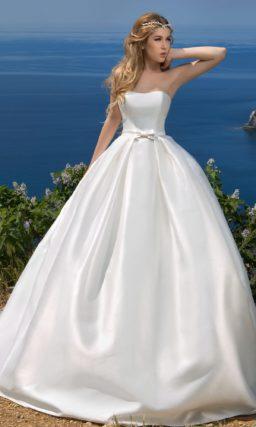 Атласное свадебное платье с узким поясом с бантом и шлейфом сзади.
