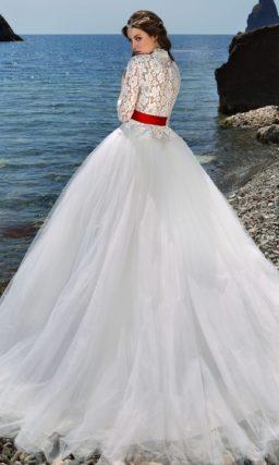 Пышное свадебное платье с длинными кружевными рукавами и алым поясом.