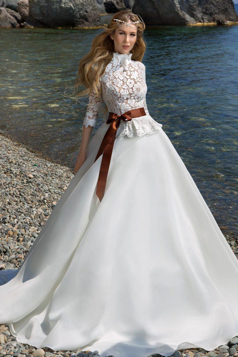 Закрытое свадебное платье с атласной юбкой и широким цветным поясом.