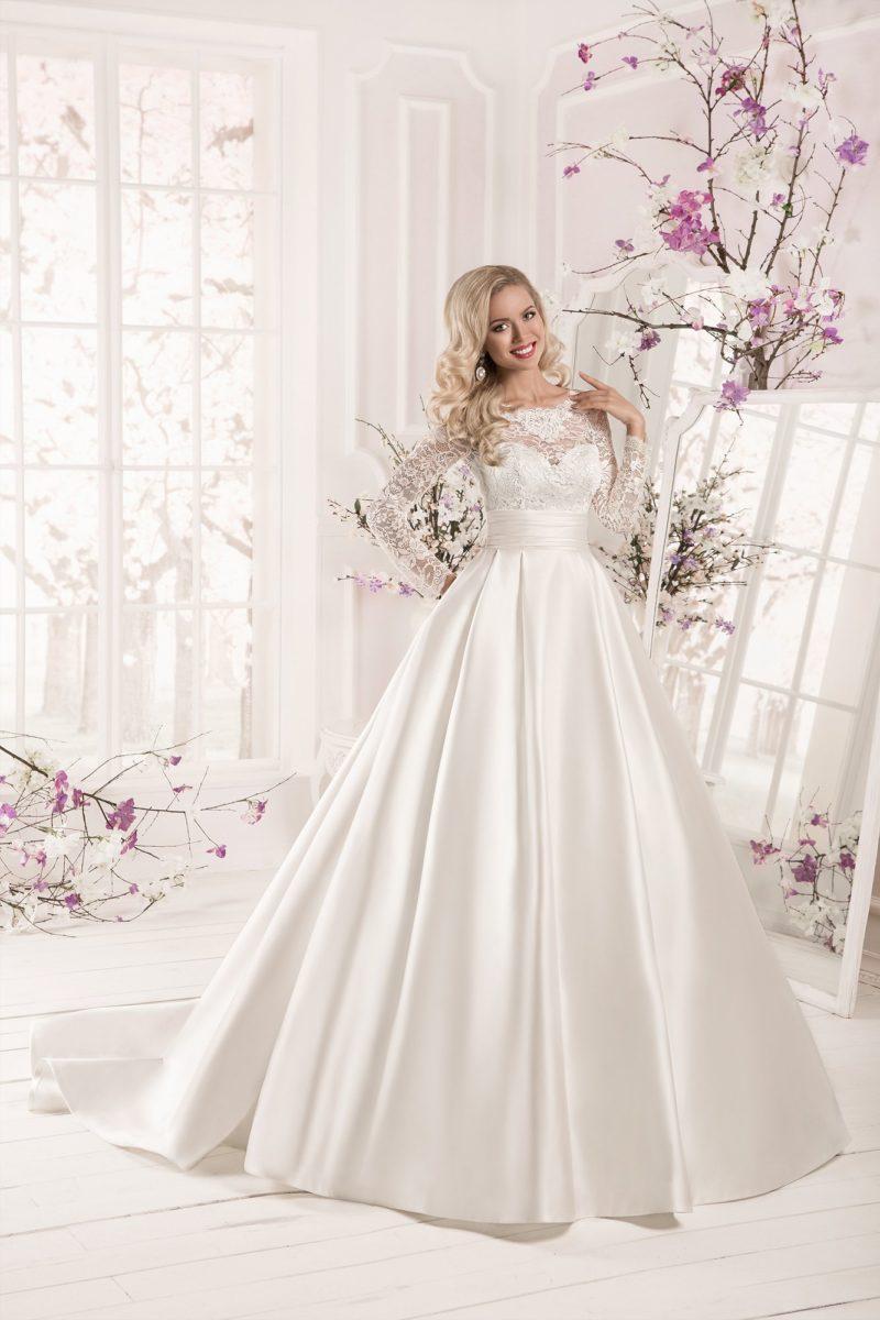 Свадебное платье из атласной ткани с широким поясом и кружевными рукавами.