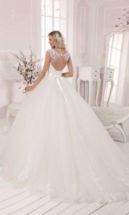 Пышное свадебное платье с атласным поясом и полупрозрачной вставкой над лифом.