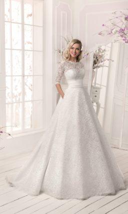 Свадебное платье силуэта «принцесса» с отделкой из плотной ажурной ткани и широким поясом из атласа.