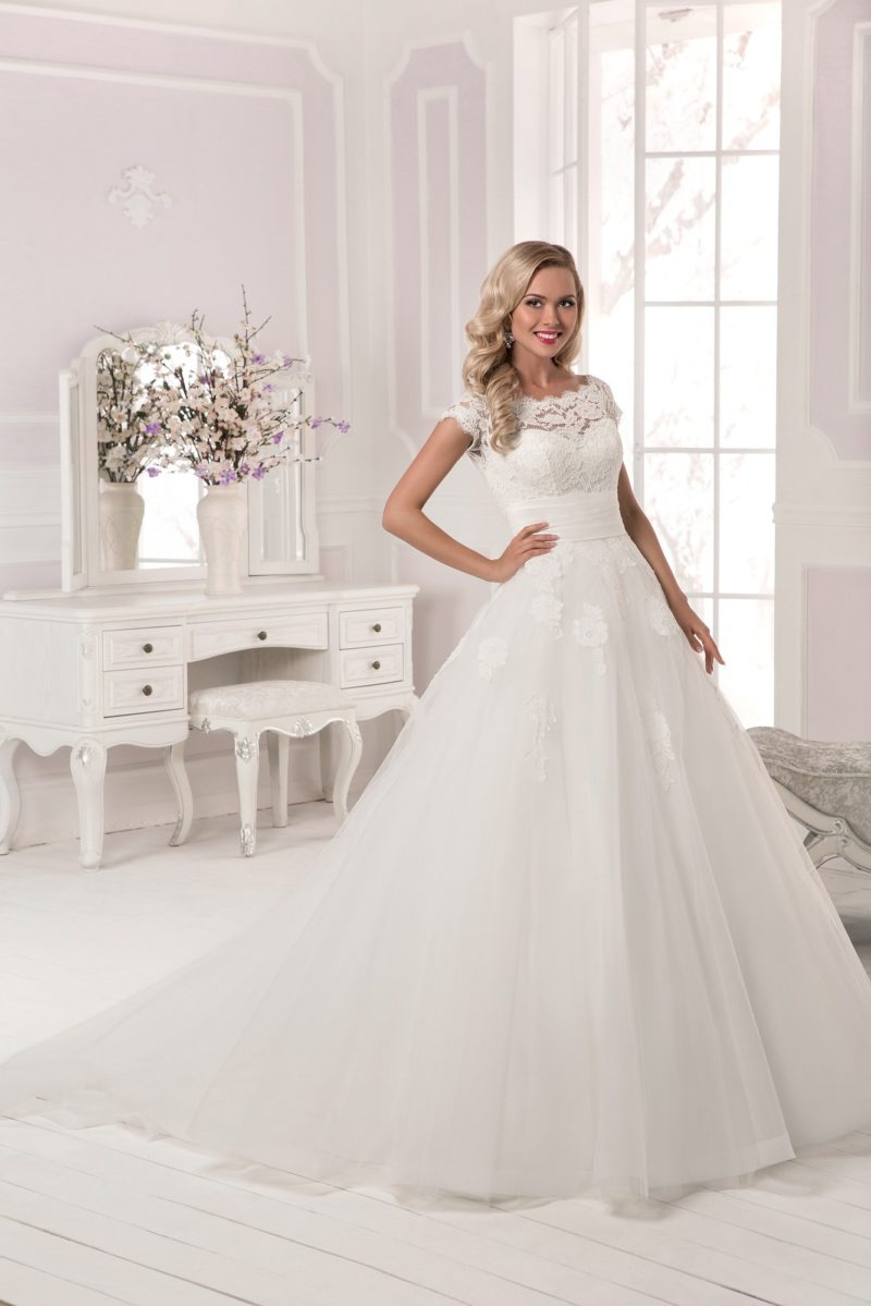 Закрытое свадебное платье с пышным силуэтом и широким поясом на талии.