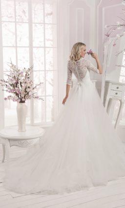 Закрытое свадебное платье с пышной полупрозрачной юбкой и широким атласным поясом.