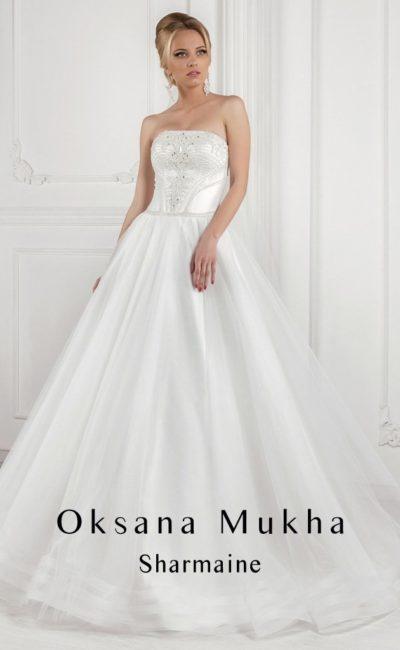 Атласное свадебное платье с юбкой А-силуэта и открытым корсетом, украшенным вышивкой.