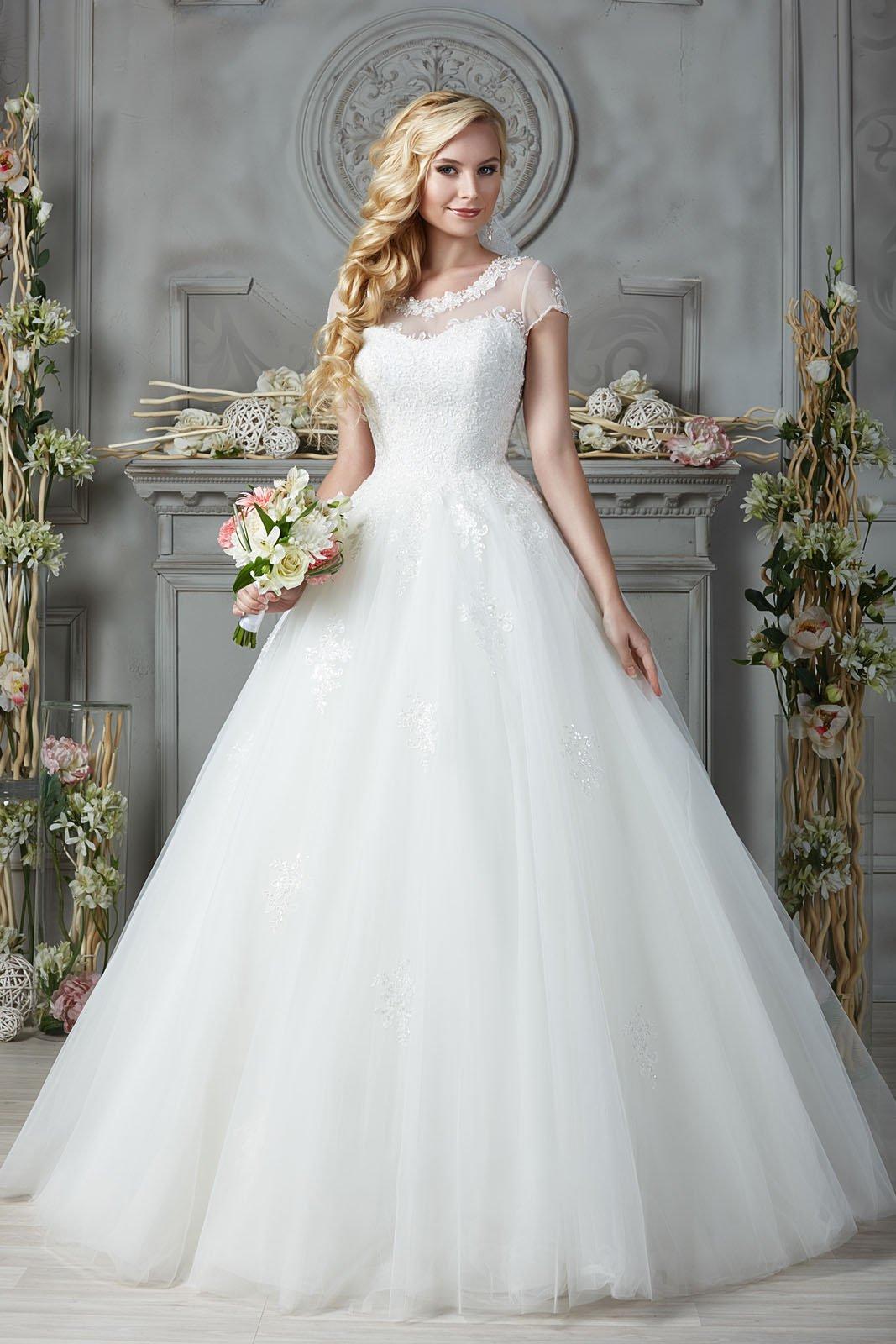 Закрытое свадебное платье с коротким рукавом, округлым вырезом и юбкой А-силуэта.