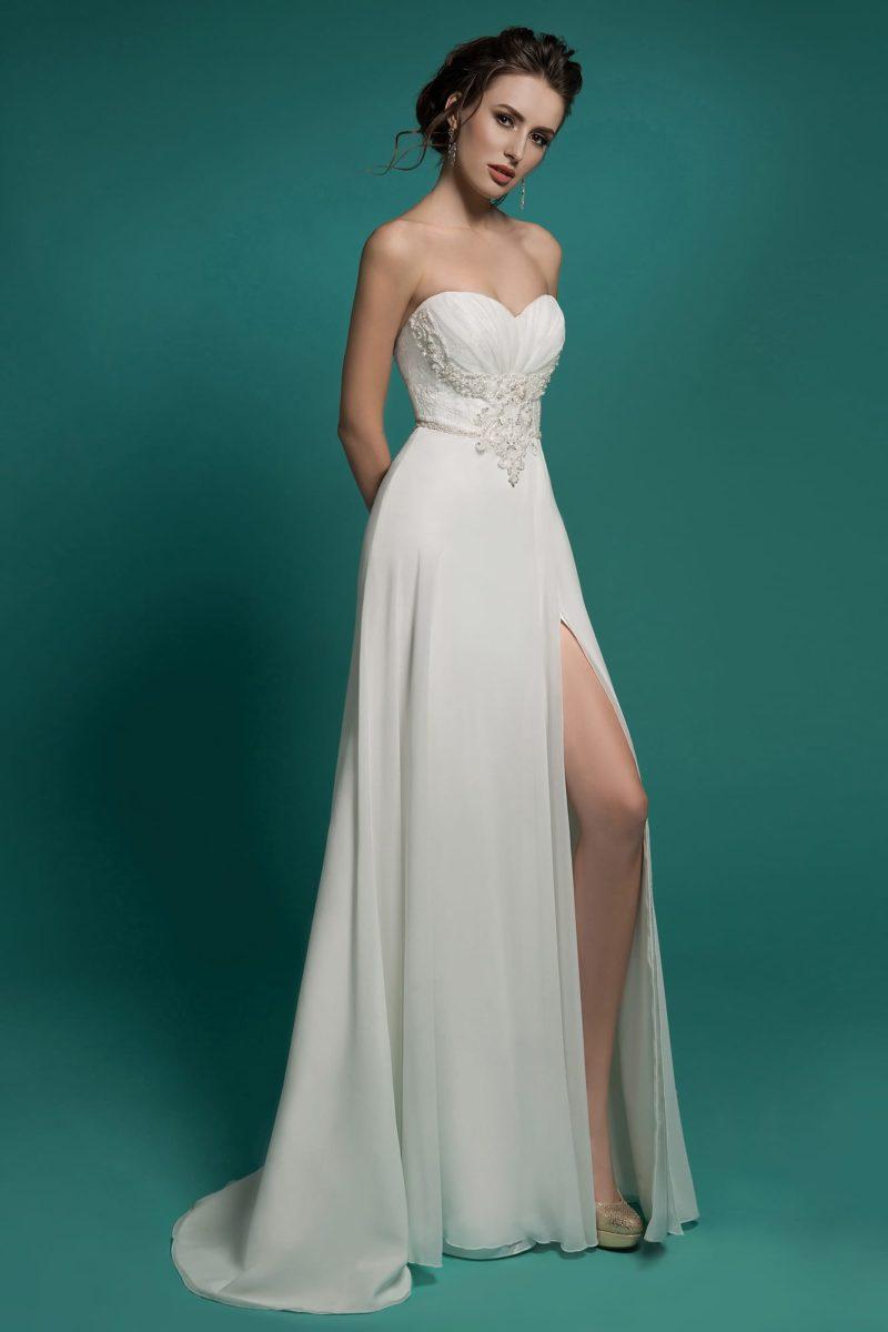 Открытое свадебное платье прямого силуэта со смелым разрезом и бисерной отделкой.