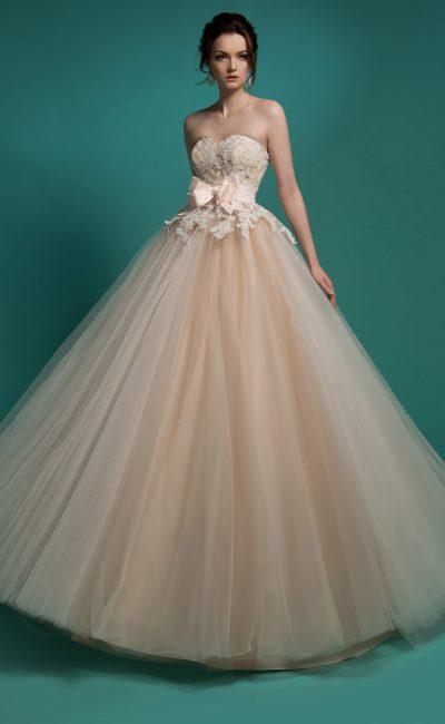 Свадебное платье бежевого цвета дополнено широким поясом.