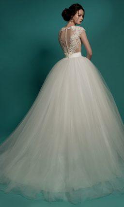 Пышное свадебное платье с полупрозрачным лифом, украшенным аппликациями.