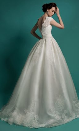 Пышное свадебное платье с объемной верхней юбкой и глубоким вырезом.