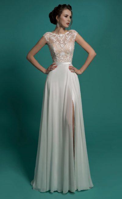 Прямое свадебное платье с драматичным разрезом на юбке и бежевым корсетом.