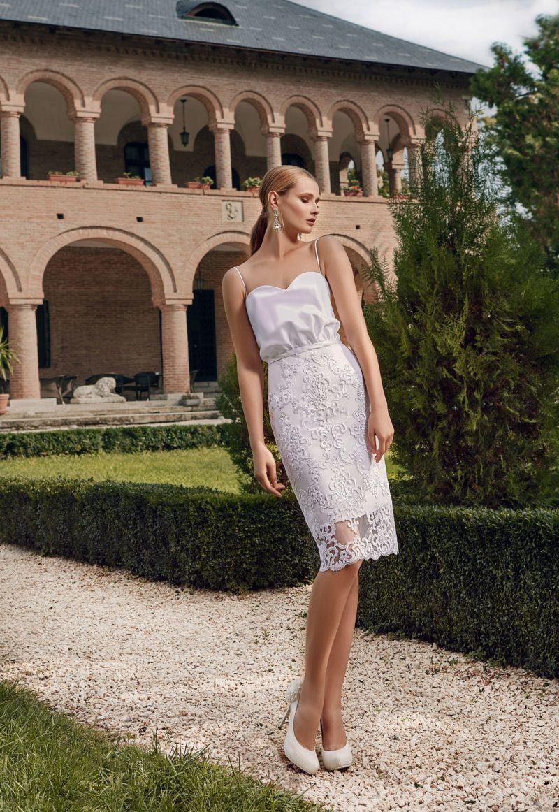 Открытое свадебное платье длиной до колена с лифом из атласа и кружевной юбкой.