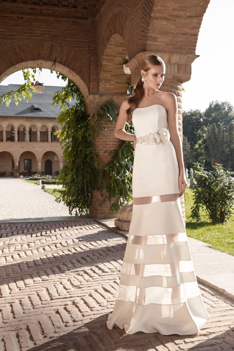 Прямое свадебное платье с несколькими полупрозрачными вставками по подолу.