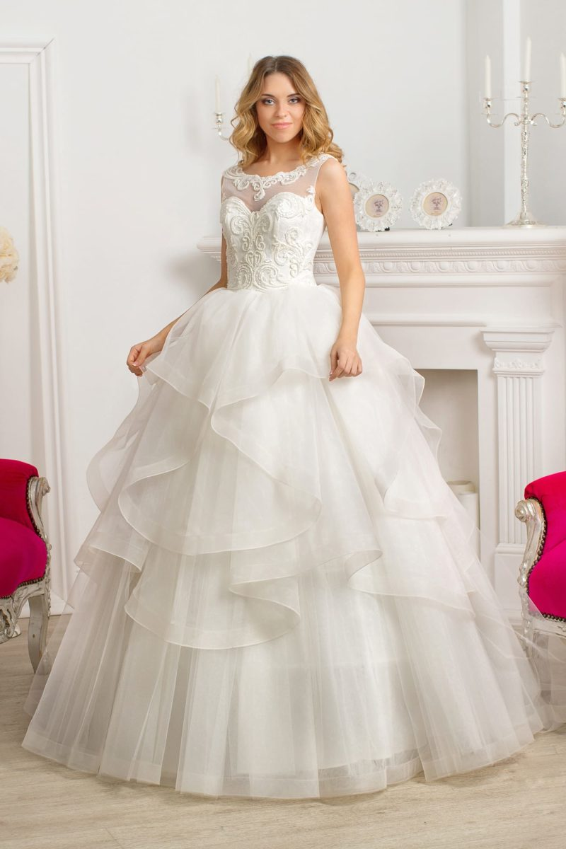 Пышное свадебное платье с юбкой, покрытой полупрозрачными оборками.