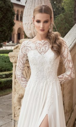 Прямое свадебное платье с высоким разрезом на юбке и длинными рукавами.