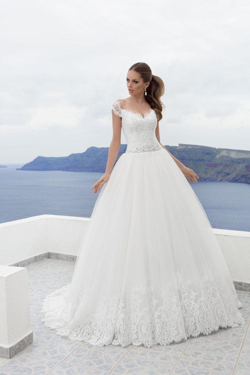 Пышное свадебное платье с ажурным корсетом и полосой кружева по нижней части подола.