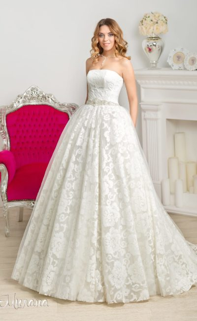Пышное свадебное платье с открытым корсетом и шлейфом, отделанное кружевом с крупным рисунком.