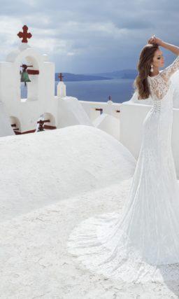 Прямое свадебное платье по всей длине покрыто кружевом и дополнено широким поясом.