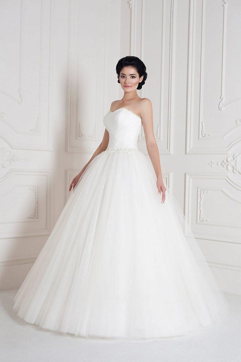 Свадебное платье с изящно драпированным корсетом и многослойной юбкой на подкладке.