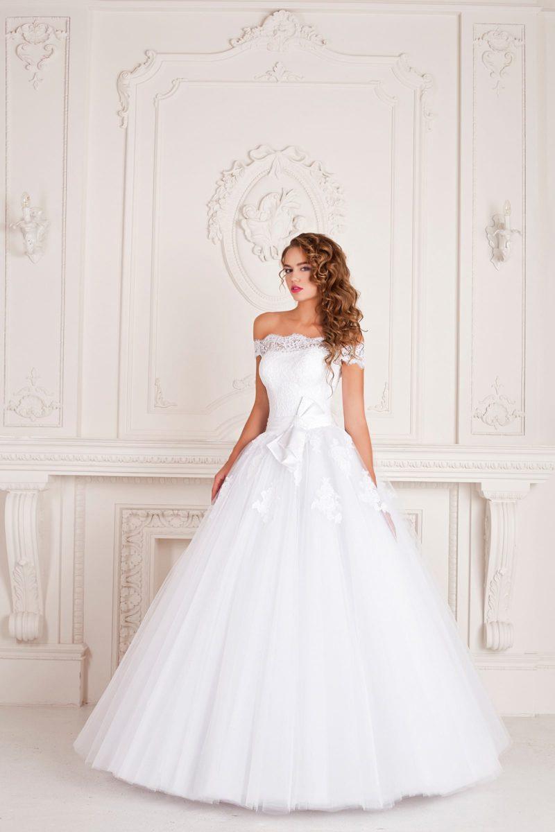 Торжественное свадебное платье с драматичным портретным декольте и бантом на талии.