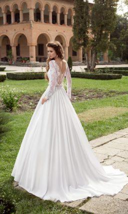 Пышное свадебное платье с длинными рукавами из кружева и узким сверкающим поясом.