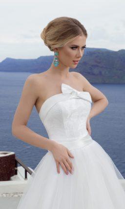 Открытое свадебное платье силуэта «принцесса» с атласной отделкой и бантом на лифе.