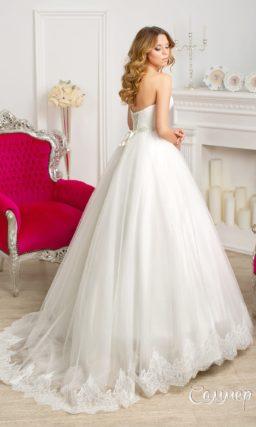 Открытое свадебное платье с драпировками на корсете и пышной юбкой с кружевом снизу.