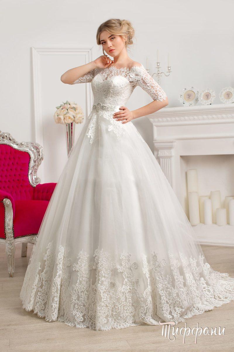 Пышное свадебное платье с ажурным верхом, дополненным короткими облегающими рукавами.