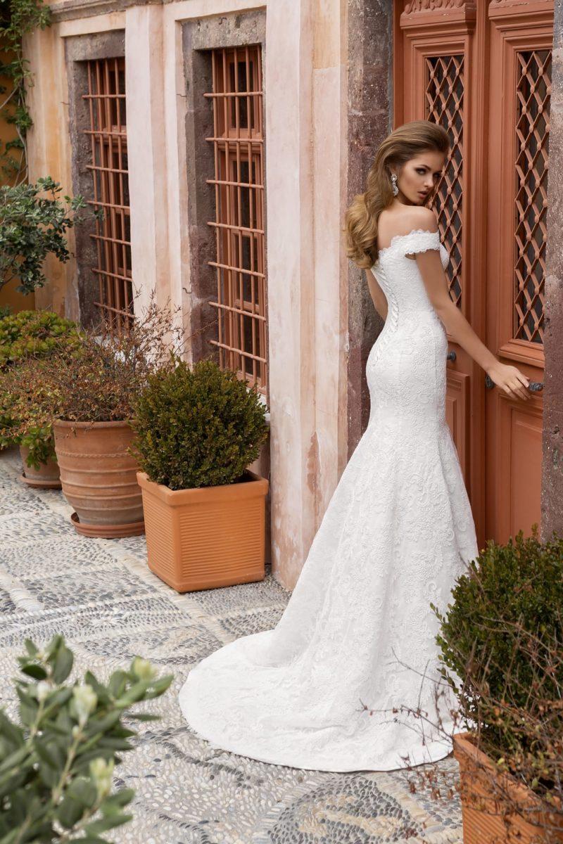 Свадебное платье силуэта «рыбка» с роскошным кружевным шлейфом и портретным декольте.