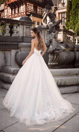 Пышное свадебное платье с лифом оригинальной формы и узким атласным поясом.