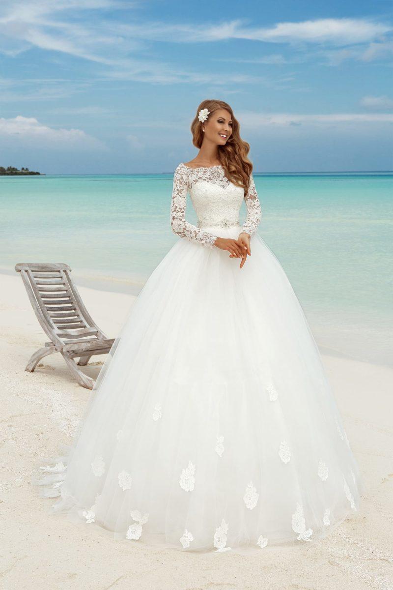 Пышное свадебное платье с верхом из плотного кружева и длинными рукавами.