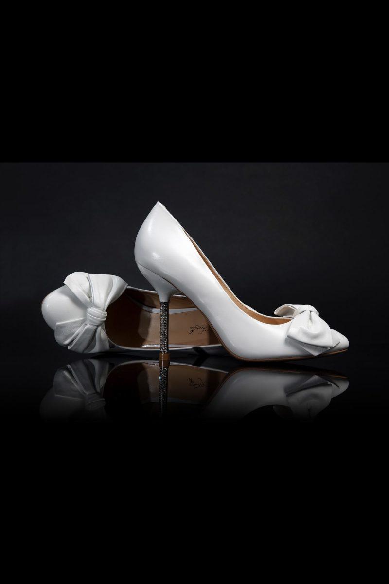 Туфли из белой глянцевой кожи, украшенные бантами, с каблуком 12 см.