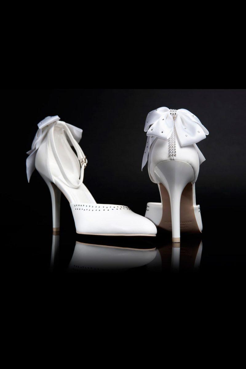 Выразительные свадебные босоножки с высоким каблуком и бантами сзади.