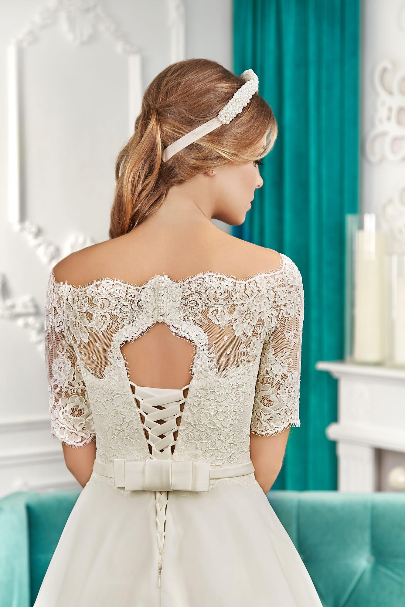 Свадебное платье силуэта «принцесса» с портретным декольте и рукавами длиной ниже локтя.