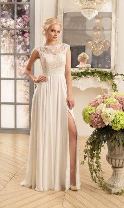 Прямое свадебное платье с разрезом на юбке и кружевной отделкой верха.