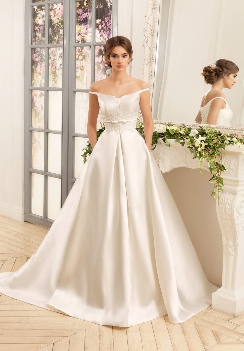 Свадебное платье А-силуэта из атласной ткани, дополненное кружевом на талии.
