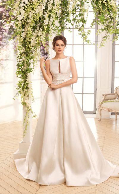 Пышное свадебное платье со шлейфом и необычными вырезами на лифе и спинке.
