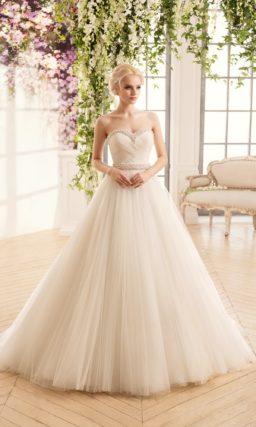 Кремовое свадебное платье А-силуэта с корсетом, украшенным драпировками и вышивкой.