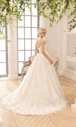 Пышное свадебное платье цвета слоновой кости с кружевной отделкой.