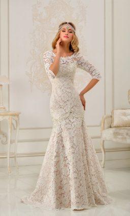 Свадебное платье силуэта «рыбка», по всей длине покрытое белым кружевом на бежевой подкладке.