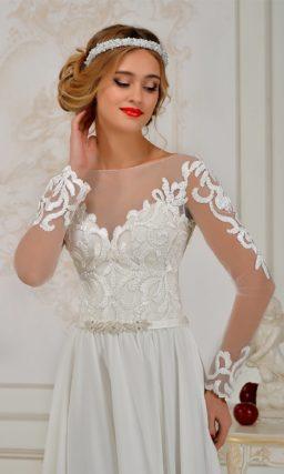 Прямое свадебное платье с высоким разрезом и длинным рукавом с крупной отделкой.