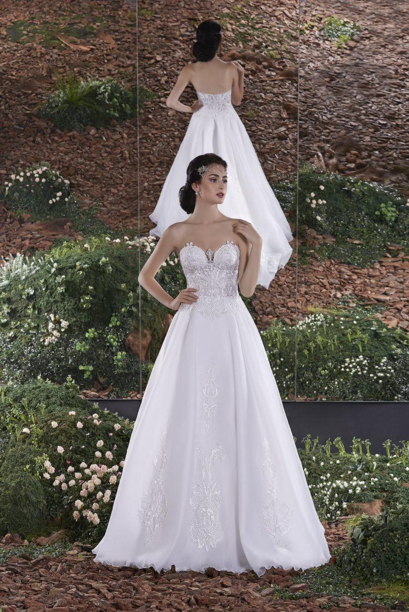 Открытое свадебное платье силуэта «принцесса» с лифом, покрытым глянцевым кружевом.