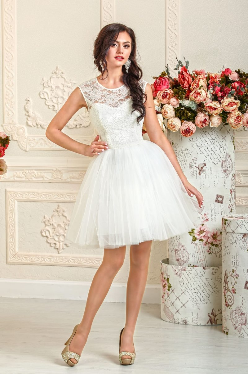 Закрытое свадебное платье с пышной юбкой длиной до середины бедра.