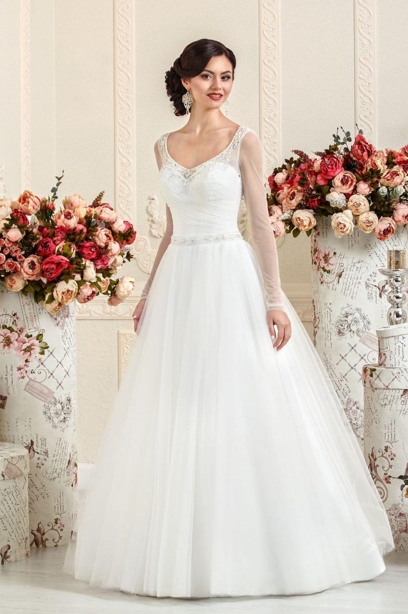 Пышное свадебное платье с длинными прозрачными рукавами и вышивкой по краю декольте.